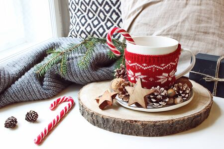 Winter morning breakfast still life scene. Cup of coffee, tea with candy canes standing near window on wooden cut board. Decorated by pine cones, hazelnuts and wooden stars. Christmas concept.