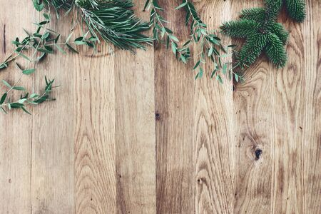 Christmas background. Border, frame of green fir, eucalyptus and pine tree branches on old wooden oak table. Winter festive banner. Vintage look. Flat lay, top view.