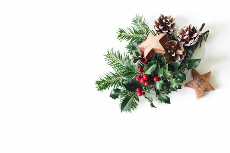 Christmas festive styled composition. Winter floral arrangement. Pine cones, fir tree branches, red holly berries and wooden stars and on white table background. Flat lay, top view. Zdjęcie Seryjne
