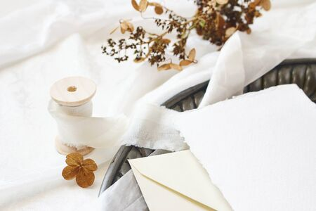 Greeting card, envelope, dry hydrangea flowers and silk ribbon on old vintage tray. White silk fabric background. Zdjęcie Seryjne - 132116059