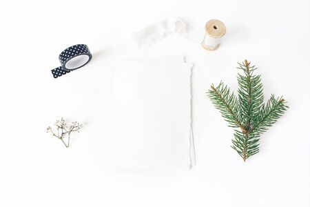 Christmas, winter wedding desktop stationery mock-up scene. Blank greeting card, envelope, black washi tape, silk ribbon and green spruce tree branch.White table background. Flat lay, top view.
