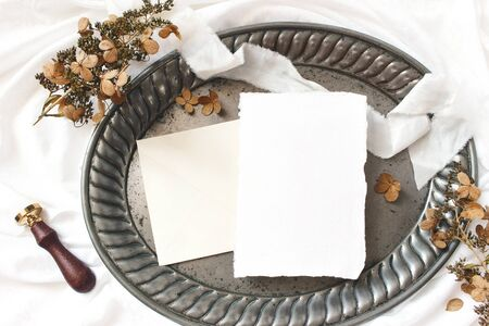 Styled stock photo. Winter, fall wedding, birthday table composition. Stationery mockup scene. Greeting card, envelope, dry hydrangea flowers and ribbon on old vintage silver tray. Flat lay, top view. Zdjęcie Seryjne