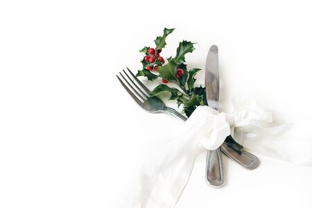 Christmas table setting. Silver cutlery, holly berry branche and silk ribbon isolated on white background. Winter wedding or restaurant menu concept. Flat lay, top view. Stock Photo