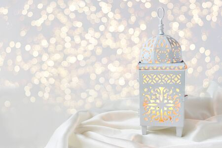 Ornamental white Moroccan, Arabic lantern on silk textile throw. Burning candle, glittering bokeh lights. Greeting card for Muslim community holy month Ramadan Kareem. Festive background. Фото со стока