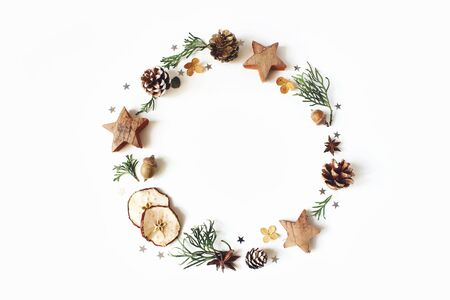 Christmas circle floral composition. Wreath of cypress branches, pine cones, anise, confetti stars, dry apples and hydrangea flowers on white background. Winter wedding design. Flat lay, top view.