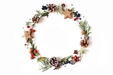 Wreath of cypress, eucalyptus branches, pine cones, rowan berries, anise, confetti stars and sea holly flowers on white background. 写真素材