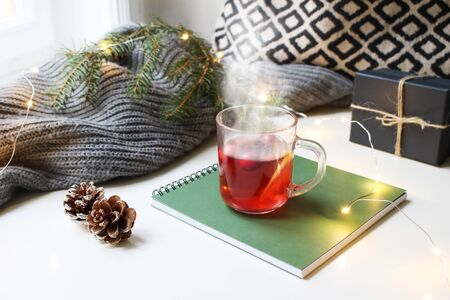 Cozy Christmas morning breakfast scene. Steaming glass cup of hot fruit tea standing near window on note pad. Glittering lights, pine cones, gift box and Christmas tree branch on wool plaid.