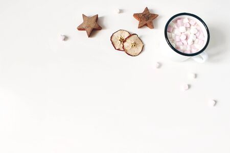 Christmas corner composition. Hot chocolate in enamel mug. Marshmallow,wooden stars, dry apple fruit slicess on white wooden table background. Winter breakfast. Flat lay, top view. Empty space.