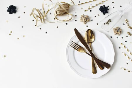New Year, Christmas styled glamorous black and gold table setting with plate, goldenware, confetti stars and champagne glass. Party decoration, flat lay, top view. Empty space. Restaurant menu concept