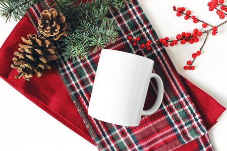 Winter still life. Blank coffee mug, fir tree branch, holly berries and pine cones. Checkered tartan plaid. Christmas traditional styled composition, rustic scene. Product mockup. Flat lay, top view. Banco de Imagens