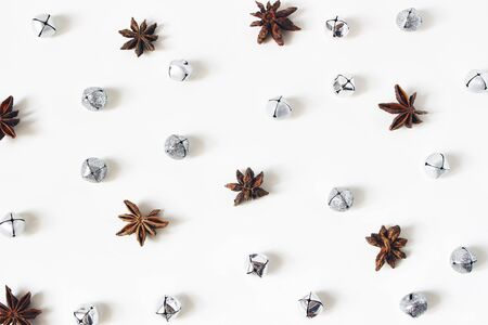 Christmas styled stock composition. Glittering silver jingle bells and anise stars on white background. Flat lay, top view. Winter decorative pattern.