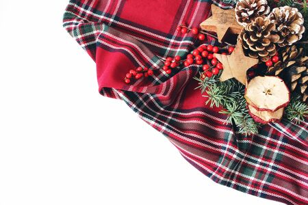 Christmas festive styled composition. Winter floral arrangement. Pine cones, fir tree branches, red holly berries and wooden stars and on checkered tartan plaid. White table background. Flat lay, top Banco de Imagens