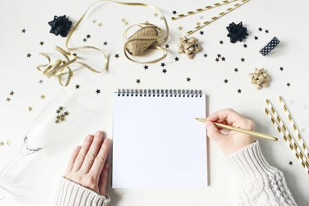 Female hands in sweater and writing. New year resolution, wish list concept. Blank paper letter mockup. Golden party decoration, confetti and wine glass on white table background. Flat lay, top view.