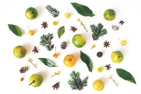Christmas styled composition. Tangerine citrus fruit and leaves, fir tree branches, anise stars, holly berries and little apples on white table background. Winter holiday pattern. Flat lay, top view. Stock fotó