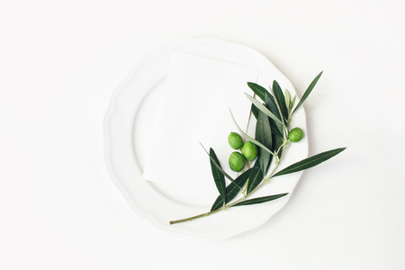 Festive table summer setting with olive leaves, branch and fruit on porcelain plate. Blank paper card mockup scene. Mediterranean wedding or restaurant menu concept. Flat lay, top view.