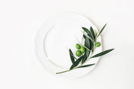 Festliche Tischsommereinstellung mit Olivenblättern, Zweigen und Früchten auf Porzellanteller. Mockup-Szene für leere Papierkarten. Mediterranes Hochzeits- oder Restaurantmenükonzept. Flache Lage, Ansicht von oben.