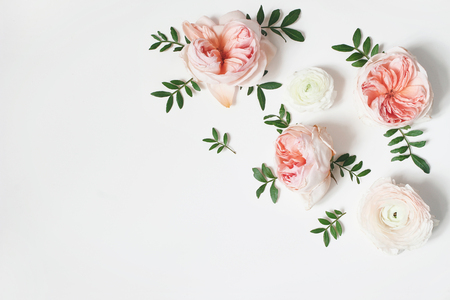 Decorative corner, floral composition with pink English roses, ranunculus and green leaves on white table background. Flower pattern. Flat lay, top view. Wedding or birthday styled stock photo. 写真素材