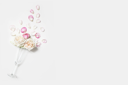 Wedding , birthday, Valentines day party composition. Champagne glass with pink rose flowers and petals isolated on white table background. Celebration, love concept. Flat lay, top view. Empty space. Banque d'images - 119805615