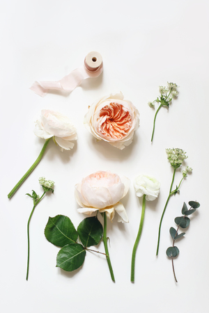 Summer botanical floral composition. Apricot English roses, ranunculus, astrantia flowers, eucalyptus branch and pink ribbon on white table background. Styled stock photo. Vertical flat lay, top view 写真素材