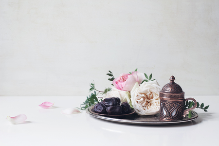 Ramadan Kareem greeting card, invitation. Plate with dates fruit, bronze coffee cup, pink roses and green branches on old silver tray. White table background. Muslim Iftar dinner. Eid ul Adha banner.