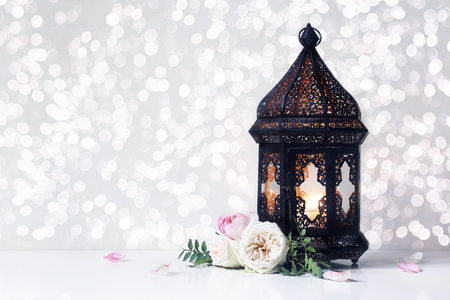Vintage black Moroccan, Arabic lantern with glowing candle, green branches, rose flowers and petals on white table background. Greeting card for Muslim holiday Ramadan Kareem with bokeh lights. 免版税图像 - 119820641