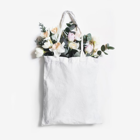 Mock-up scene of blank shopping canvas tote bag with pink tulips, daffodils flowers and eucalyptus isolated on white backfound. Spring, Easter sale. Eco friendly, zero waste concept. Flat lay, square. 免版税图像