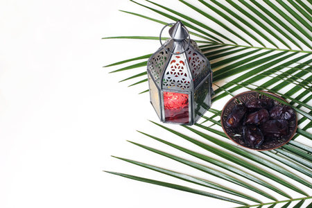 Glowing Arabic lantern, plate with dates fruit and green palm leaves isolated on white table background. Ramadan Kareem greeting card, invitation. Muslim Iftar dinner composition. Flat lay, top view.