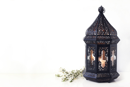 Ornamental black Moroccan, Arabic lantern with blooming prunus tree branches on white table. Greeting card for Muslim community holy month Ramadan Kareem. Festive background.
