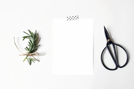 Feminine stationery, desktop mock-up scene. Blank greeting card, washi tape, black vintage scissors and rosemary herb.White table background. Flat lay, top view. Rustic composition.