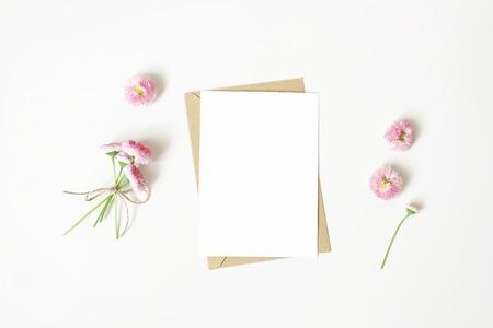 Papeterie féminine, scène de maquette de bureau. Carte de voeux vierge verticale, enveloppe en papier craft et bouquet de marguerites et fleurs isolées sur fond de tableau blanc. Mise à plat, vue de dessus. Composition rustique.