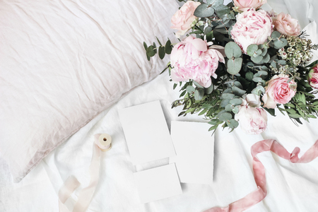 Cozy bedroom still life scene. Wedding, birthday bouquet of pink roses, peony flowers and eucalyptus branches. Silk ribbons on linen bedding. Blank greeting cards mockups. Top view.