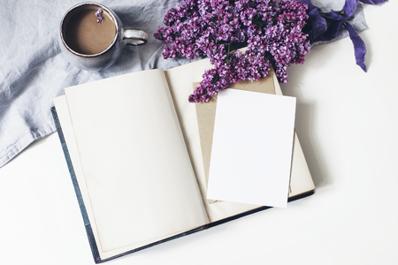 Spring feminine scene, floral composition. Bunch of purple and white lilac flowers, old book, cup of coffee and linen tablecloth on white background. Blank greeting card mockup. Flat lay, top view.