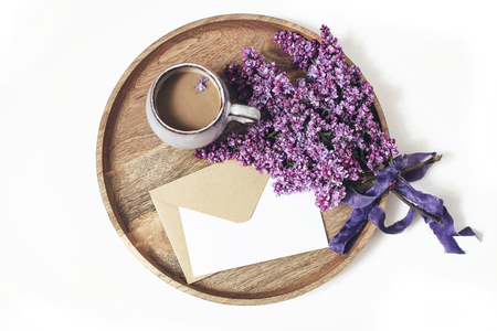 Spring breakfast scene. Blooming purple lilac branches, silk ribbon, cup of coffee and wooden tray isolated on white table background. Blank greeting card and envelope mockup. Flat lay, top view. Imagens