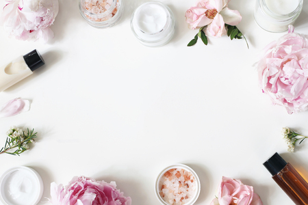 Styled beauty frame, web banner. Skin cream, shampoo, tonicum bottles, leaves, rose, peony flowers and salt on hite table background. Organic cosmetics, spa concept. Empty space, flat lay, top view. Banco de Imagens