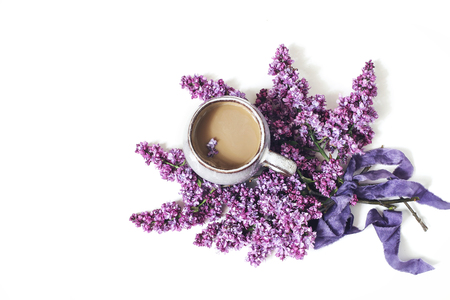 Styled spring breakfast scene, feminine floral composition. Bouquet of purple lilac branches, silk ribbon and cup of coffee isolated on white table background. Flat lay, top view. Imagens