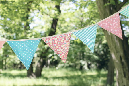 Close up of bunting flags hanging among trees. Summer garden party. Outdoor birthday, wedding decoration. Midsummer, festa junina concept. Selective focus. Natural blurred background.