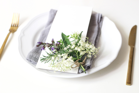 Close up of festive table summer setting.Golden cutlery, porcelain plate, blank menu card, napkin and herbs bouquet. Mediterranean wedding or restaurant concept. Selective focus, blurred background.