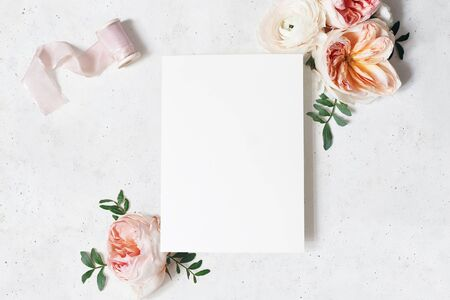 Feminine wedding, birthday stationery mock-up scene. Blank paper greeting card with bouquet of green leaves, blush pink English roses and ranunculus flowers. Concrete table background. Flat lay, top 写真素材
