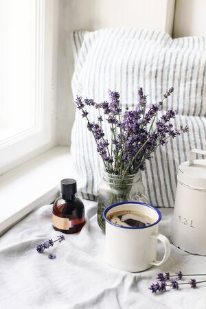 French summer still life. Cup of coffee, lavender flowers bouquet, essence oil bottle on windowsill. Feminine styled stock photo, floral composition with Lavandula officinalis herbs, rustic scene, vertical