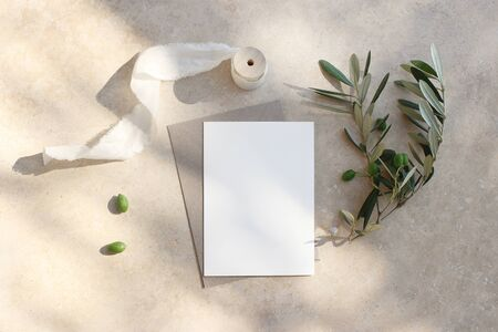 Summer wedding stationery mock-up scene. Blank greeting card, invitation. Craft envelope, olive fruit, branch and silk ribbon. Elegant marble background in sunlight, shadows. Flat lay, top view. Фото со стока