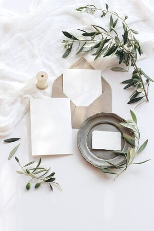 Summer wedding stationery mock-up scene. Blank greeting cards, envelope, vintage silver plate, olive branches and ribbon. White background with cotton table runner in sunlight. Flat lay, top view.