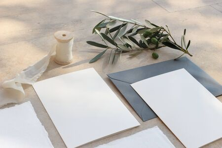 Closeup of summer wedding stationery mock-up scene. Blank greeting cards, invitations, envelopes, olive branch and silk ribbon. Marble background in sunlight, shadows. Top view.