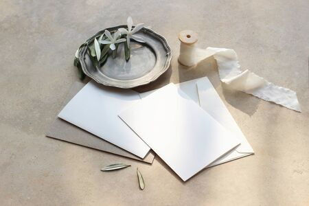 Summer wedding stationery mock-up scene. Blank greeting cards, envelopes, silver plate with olive branch and white flowers and silk ribbon. Marble background in sunlight, shadows. Top view.