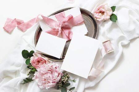 Feminine wedding, birthday mock-up scene. Blank paper greeting cards, envelope, eucalyptus, pink roses, peony flowers and ribbons on white table background. Light, shadow play. Flat lay, top view Stock fotó