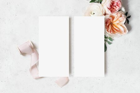 Wedding, birthday stationery mock-up scene. Blank menu cards. Decorative floral corner. Green leaves, pink English roses, ranunculus flowers and ribbon. Concrete table background. Flat lay, top view