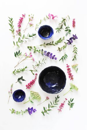 Handmade organic pottery. Ceramic plates and bowls isolated on white table backgound. Summer floral composition of erica, sage, sedum flowers, eucalyptus leaves and branches. Flat lay, top view.