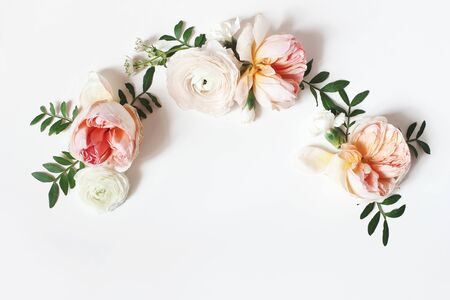 Decorative wreath, floral garland, composition with pink English roses, ranunculus and green leaves on white table background. Flower pattern. Flat lay, top view. Wedding, birthday styled stock photo.