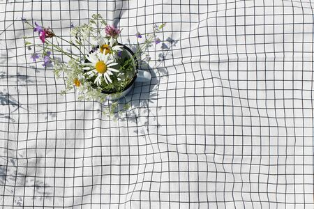 Mug with wild fowers bouquet. Bells, cow parsley and daisies on white checkered blanket, plaid in sunny day. Spring, summer outdoor meal, relaxation concept. Flat lay, top view, empty copy space.