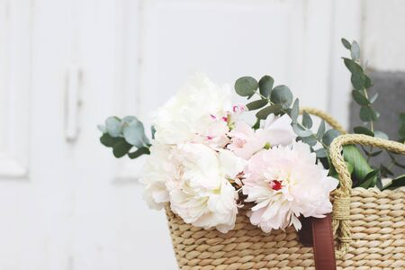 Feminine wedding still life composition. Straw French basket bag with pink peonies flowers and eucalyptus bouquet. Old white door in the background. Styled stock photo. Selective focus.