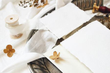 Winter, fall styled wedding, birthday table composition. Stationery mockup scene. Closeup of greeting cards, envelope, dry hydrangea flowers and ribbon on old vintage silver tray. Selective focus. Stock fotó